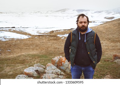 Man in the winter steppe looking at camera
