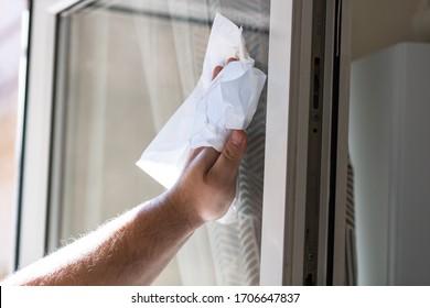 Man wischt Fenster mit Papierhandtücher, Reinigungsservice Konzept. Haushaltsarbeit und Haushaltsführung