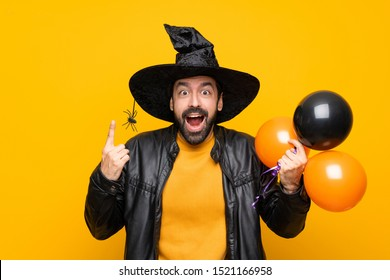 Man with witch hat holding black and orange air balloons for halloween party pointing up a great idea