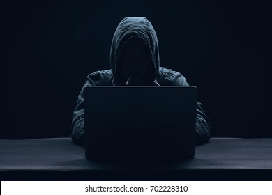 A man without a face behind a laptop, a hacker attack