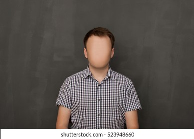 Man Without a Face. The guy in a checkered shirt without a face against a black wall. strange unusual portrait of the dude. self-portrait artist photographer
