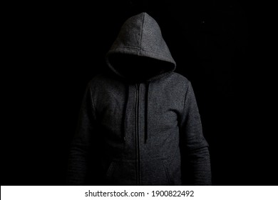 Man without a face in a hood on a dark background.