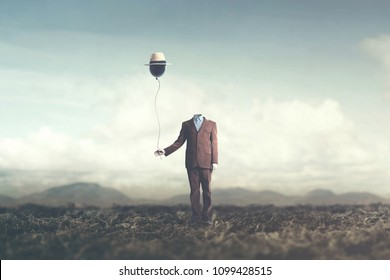 man without head holds black balloon with hat surreal concept