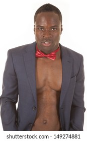 A man without a shirt in a suit coat and a bow tie.
