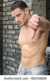 Man without a t-shirt shows a hand thumbs down