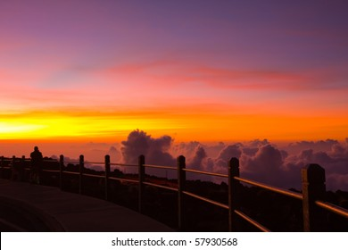 A man is witnessing the unforgettable beauty of a sunset viewed from the top of the Haleakala Volcano, Maui, Hawaii