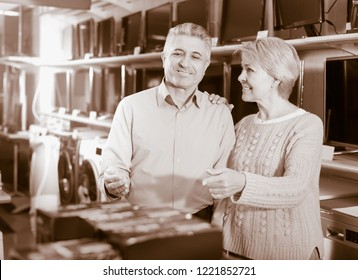 Man and woman 49-54 years old are choosing home appliances and consumer electronics in mall.