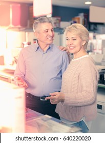 Man and woman 49-54 years old are visiting shop of household appliances for buying goods for kitchen and house.