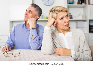 Man and woman 50-54 years old are offended at each other because of the misunderstanding in his home.