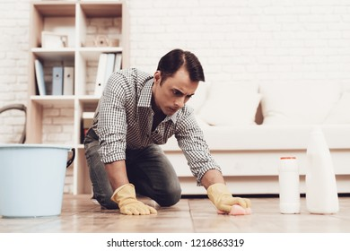 Man and Woman in Apartment. Man Cleans Room. Man with Vacuum Cleaner. Male Washes Brown Floor. Male with Washcloth in Hands and Bucket. Woman Control Cleaning Rrocess. Cleaning Process.