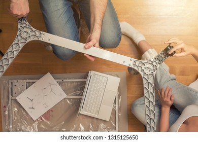 Man and woman assembling furniture  on wooden parquet using instruction for for self assembly