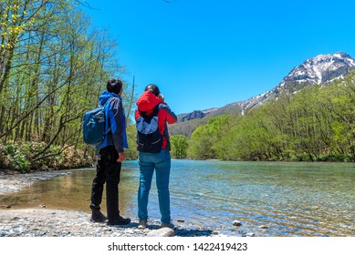Man and woman with Azusa river and Mount Yake on background at Kamikochi in Northern Japan Alps.