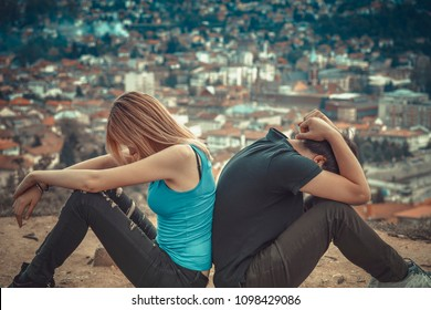 Man and woman back to back, turned their back on each other, surrounded by a mountain view, their relationship about to fall apart and break up