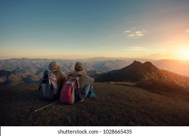 man and woman backpacker sitting on top of high moutain with panorama view of mountain scape