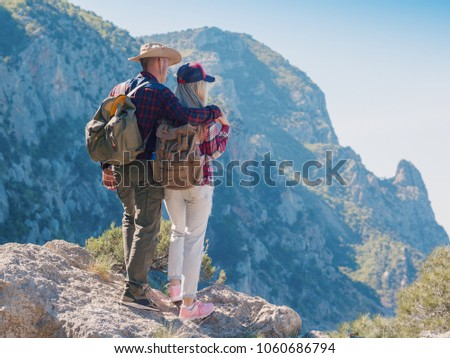 d2068511013 Man and woman backpackers standing and hugging on the mountain. Couple  hikers with backpacks relaxing on top of a hill and enjoying sea view and  cliffs.