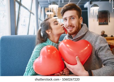 man and woman with balloon in the form of heart in a cafe. woman kisses a man on the cheek. Couple in love on a date. Love story and Valentines Day concept