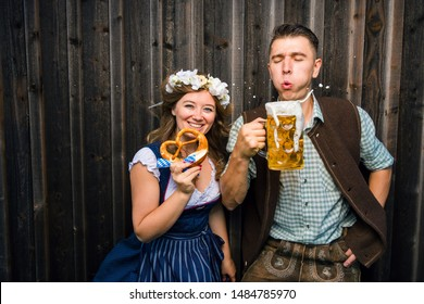 Man and woman in Bavarian costume drinking beer