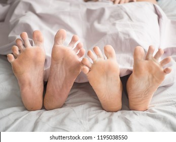 a man and a woman in bed. male and female feet on a grey linens.