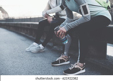 Man and woman before urban workout. Couple preparing for running and sitting on the bench on the street