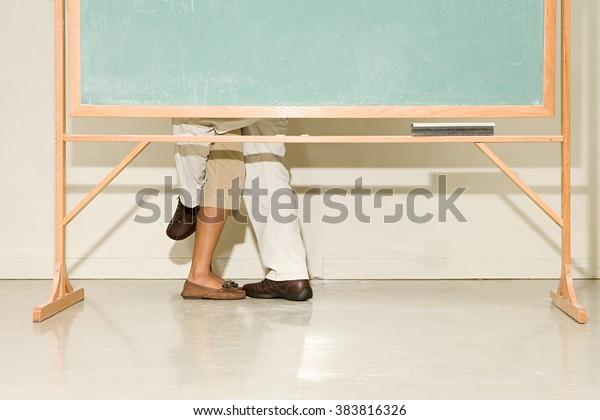 Man and woman behind a blackboard