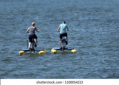 man and woman from behind ride with floating pedal bicycle boats across the blue lake, holiday and leisure activity, copy space