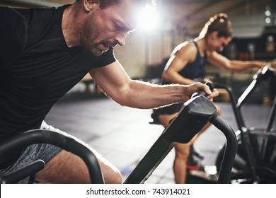 Man and woman behind riding cycling machine in hard efforts grimacing in light spacious gym.