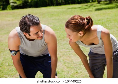 Man and a woman bending over as they recover while looking at each other