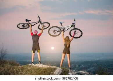 Man and woman bikers holding bikes high up in the sky on the top of a hill against magnificent sunset with blurred background. Pink Kinesio tape glued on the girl's hand.