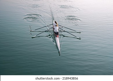 Man and woman in a boat, rowing on the tranquil lake