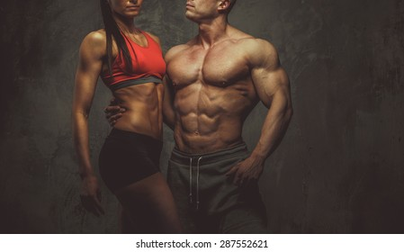 Man and woman bodybuilders couple posing on grey background