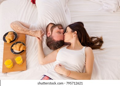 a man with a woman breakfast in bed in the morning