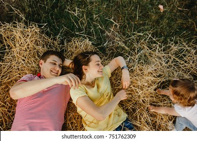 Man and woman in bright t-shirts lie on the hay with their little girl