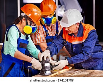 Man and woman in builder helmet with electric planer.
