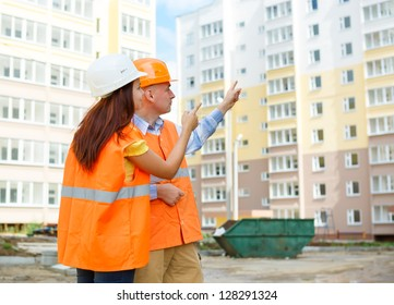 man and woman builder in a helmet on a background of construction equipment