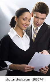 Man and woman in the business suits in the office looking at the documents