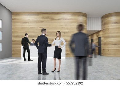 Man in woman in business suits are shaking hands in a center of an office hall. There is a white reception desk and a corridor in the background. 3d rendering