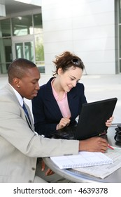 A man and woman business team communicating outside
