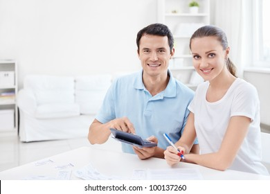Man and woman with a calculator at home