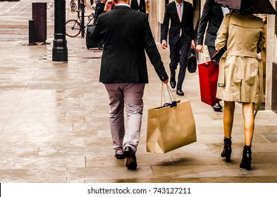A man and woman carrying shopping bags in luxury retail area of London.