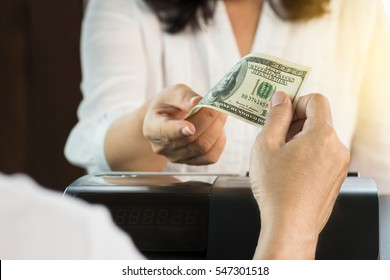 Man and woman cashier hands in white dresses holding US dollar at cash register machine.Young man paying cash  .