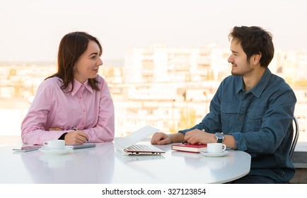 Man and Woman Casual Clothing Sitting at White Round Table with Coffee Mugs Laptop Notepads and Telephone Discussing Smiling Making Hand Notes Urban Landscape on Background