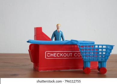 Man and woman at the checkout counter. Shopping cart and customers at the cash register. Time to pay or cash out online or at a grocery or retail store. Commerce, purchasing and payment in miniature.