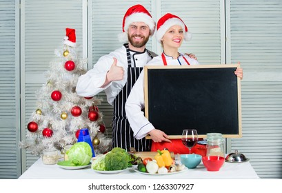 Man and woman chef santa hat near christmas tree hold blackboard copy space. Couple check list ingredients for christmas dinner. Christmas recipe concept. Menu for our family. Cooking christmas meal.