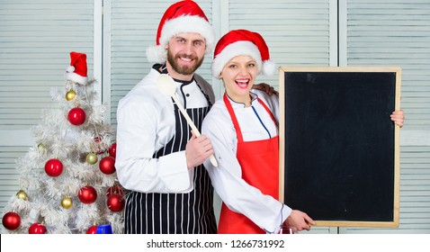 Man and woman chef santa hat near christmas tree hold blackboard copy space. Couple check list ingredients for christmas dinner. Cooking christmas meal. Christmas recipe concept. Menu for our family.
