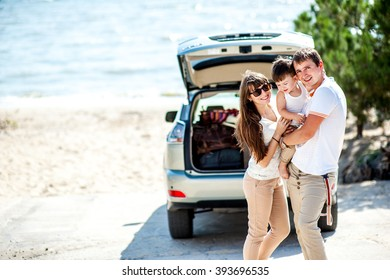 Man woman and child of three years old on the sea near the car of the jeep ready to travel