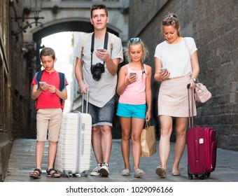 Man with woman and children are looking in phones while strolling with luggage.