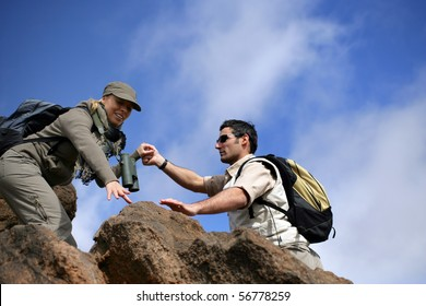 Man and woman climbing rocks