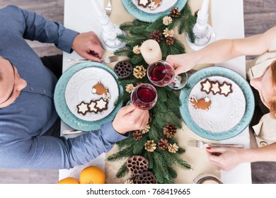 Man and woman clink glasses of wine on Christmas table with cookies and pine branches