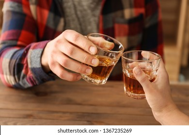 Man and woman clinking glasses of cold whisky, closeup
