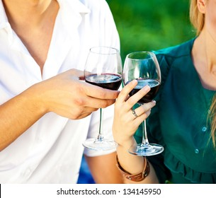 man and woman clinking glasses of wine